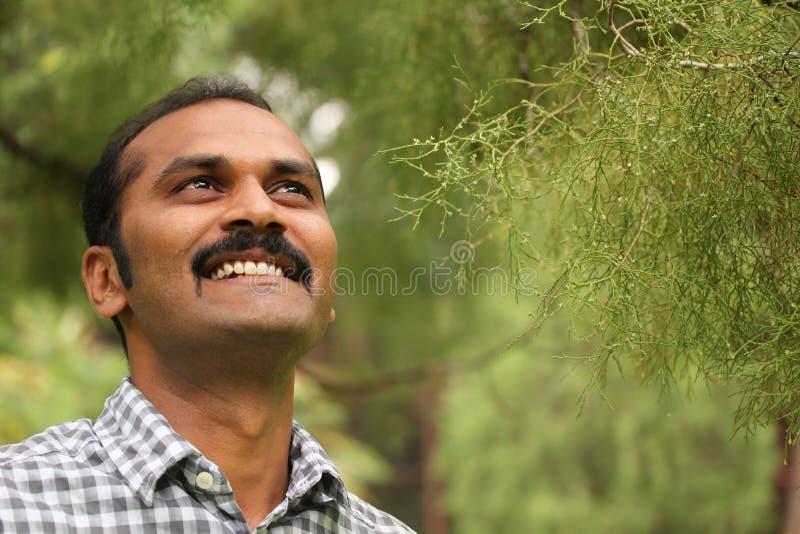 Het hoopvolle, ontspannen & gelukkige Aziatische/Indische mens glimlachen royalty-vrije stock foto