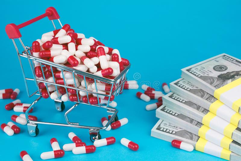 Het hoppenkarretje vulde rood geneeskrachtig capsulesgeld royalty-vrije stock afbeeldingen