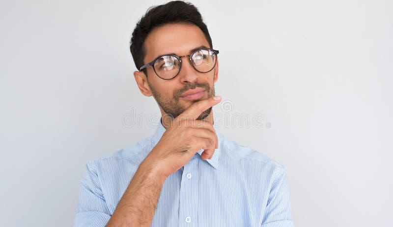 Het horizontale beeld van tevreden peinzend mannetje houdt hand onder kin, opzij kijkend, op witte studioachtergrond Succesvolle  royalty-vrije stock foto's