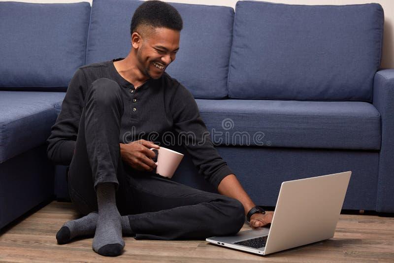 Het horizontale indoormschot van dark vilde het mannelijke stellen op vloer dichtbij blauwe bank, let op grappige video op laptop royalty-vrije stock foto