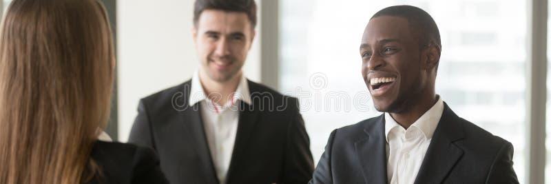 Het horizontale op de hoogte brengen beeld diverse multiraciale zakenlui komt op kantoor samen stock afbeeldingen