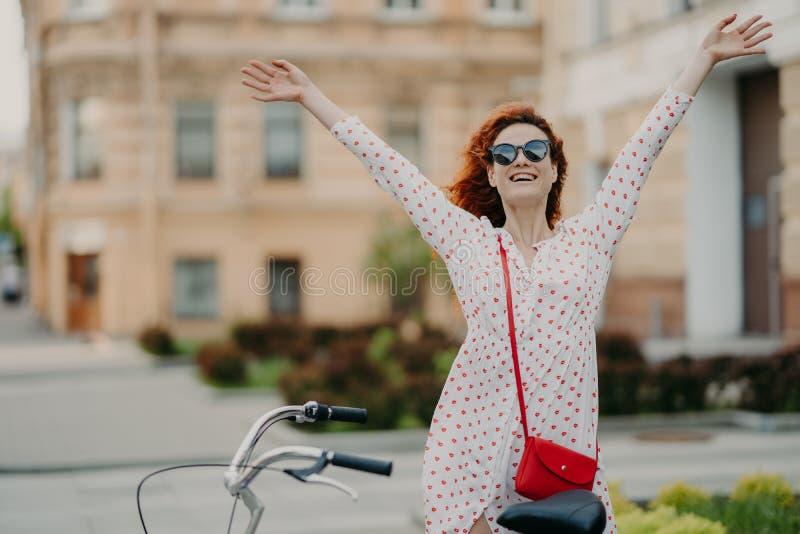 Het horizontale openluchtschot van opgetogen positieve rode haired vrouw heft handen op, voelt vrij, gekleed in de zomerkleren, r royalty-vrije stock afbeeldingen