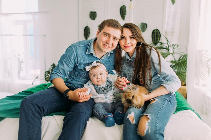 Het horizontale portret van de gelukkige familiezitting op het bed en holding de baby en het konijn stock foto's