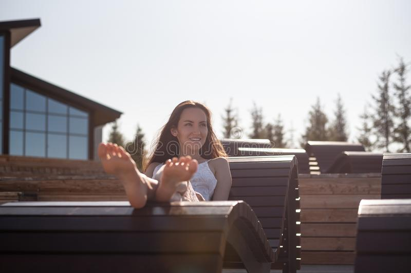 Het horizontale portret van een jonge vrouw in een witte op a liggen sunbed en kleding die glimlachen stock afbeelding
