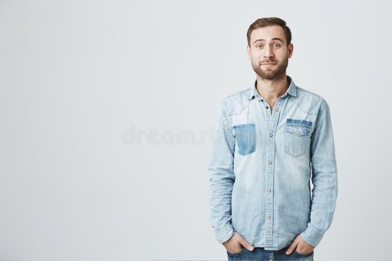 Het horizontale portret van Kaukasisch knap aantrekkelijk jong mannelijk model met stoppelveld en modieus kapsel kleedde zich bin stock foto's