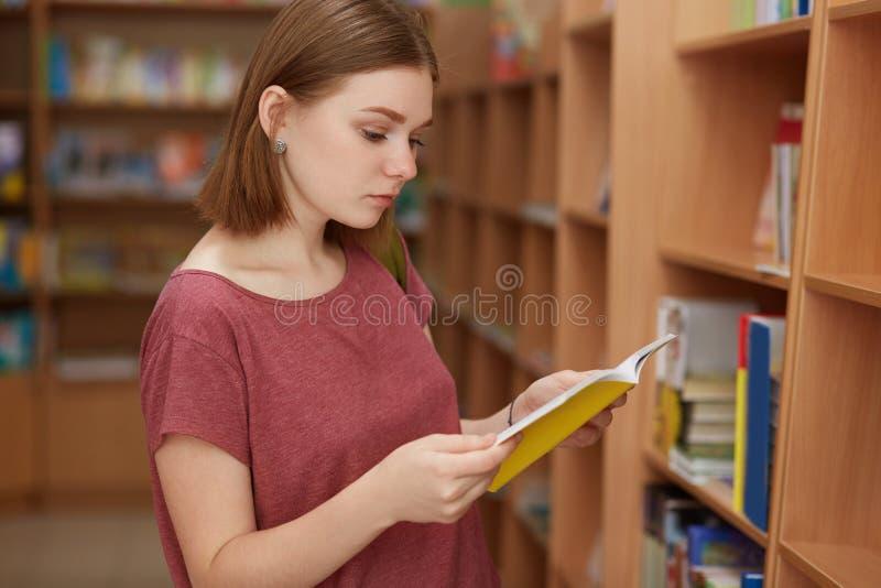 Het horizontale schot van aandachtige vrouwelijke lezer met kort kapsel, tribunes dichtbij shelfs met boeken in bibliotheek, lees royalty-vrije stock fotografie