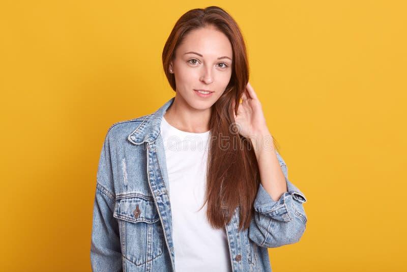 Het horizontale schot van jonge charmante vrouw in denimjasje en wit toevallig overhemd die zich over gele achtergrond bevinden,  stock foto