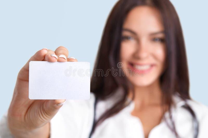 Het horizontale schot van medische arbeider houdt lege kaart, vaag silhouet, vrije ruimte voor uw naam en achternaam Leuke vrouwe stock afbeelding