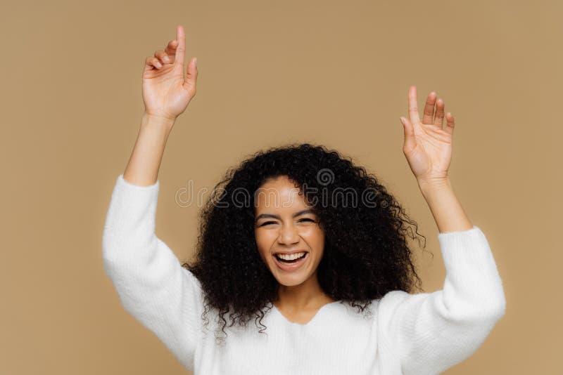 Het horizontale schot van mooi donker gevild vrouwelijk model heeft toothy glimlach, opheft handen, benadrukt, voelt extatisch, h stock afbeelding