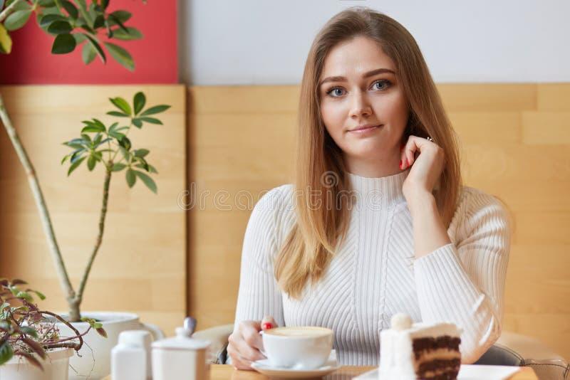 Het horizontale schot van mooi jong meisje geniet van hete espresso met heerlijk stuk van cake, heeft prettig gesprek met vriend, stock afbeelding