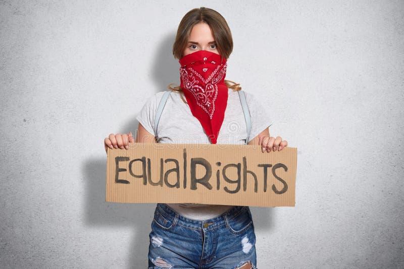 Het horizontale schot van mooi jong wijfje behoort tot feministische beweging, draagt rode bandana op gezicht, houdt plaat met in royalty-vrije stock fotografie
