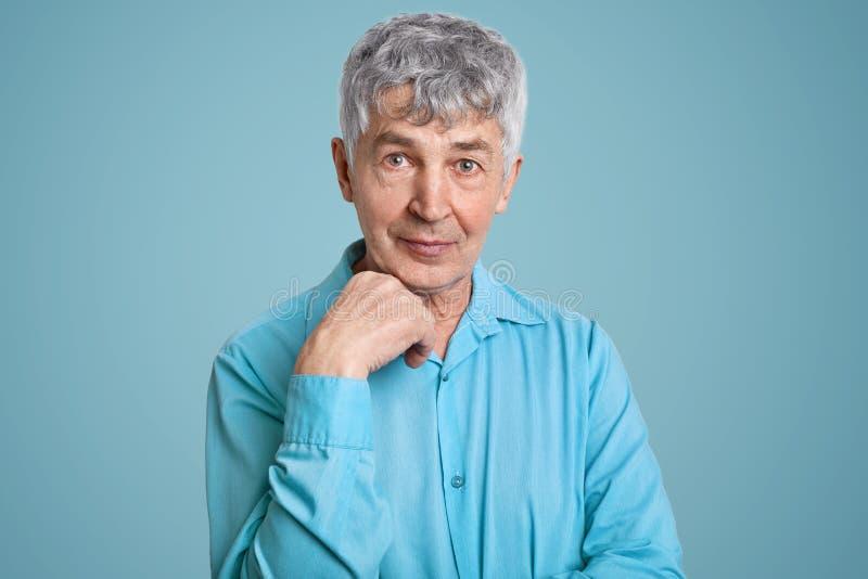 Het horizontale schot van rijpe grijze haired Kaukasische mannelijke gepensioneerde draagt elegant overhemd, houdt hand onder kin royalty-vrije stock foto's