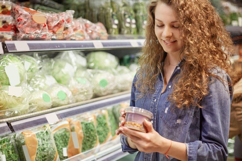 Het horizontale schot van tevreden wijfje koopt voedsel in supermarkt, leest productinformatie, kiest noodzakelijk product voor h royalty-vrije stock foto