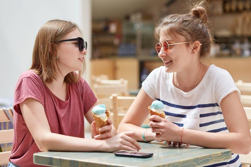 Het horizontale schot van twee vrolijke Europese meisjes draagt in zonnebril, eet koud roomijs, zit in koffie tijdens de zomertij royalty-vrije stock foto's