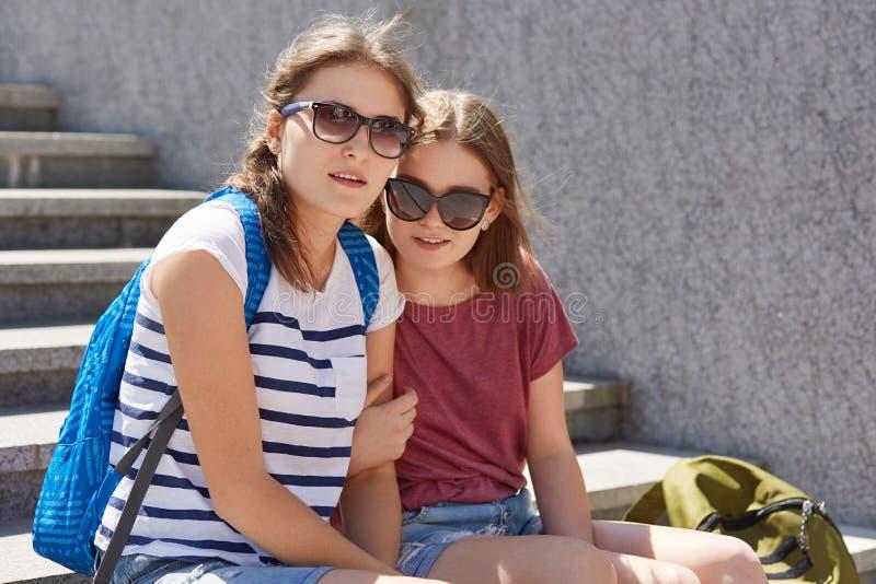Het horizontale schot van twee zusters omhelst en stelt bij camera, draagt in zonnebril, wandeling buiten, draagt rugzakken, voel royalty-vrije stock afbeelding