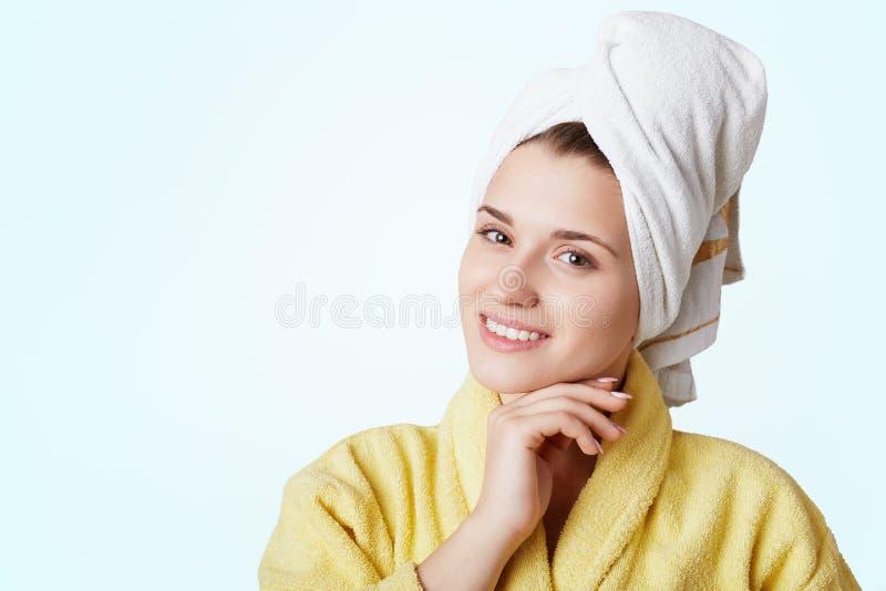 Het horizontale schot van vrolijke mooie vrouw met badhanddoek op hoofd gekleed in gele badjas, heeft net douche genomen Jonge at royalty-vrije stock fotografie