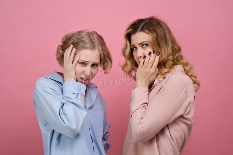Het horizontale Studioportret van twee jonge meisjes schokte met een gestoorde uitdrukking die, die zijn hoofd clutching en het g stock afbeelding