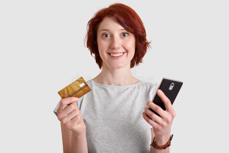 Het Horizotnalschot van tevreden vrouw met zachte glimlach, foxy haar, houdt mobiele telefoon en maakt de creditcard, geldtransac stock afbeelding