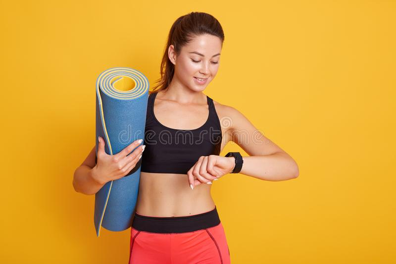 Het Horozontalschot van geschiktheidsvrouw na trainingzitting controleert resultaten op smartwatch in geschiktheid app, wijfje me stock afbeelding