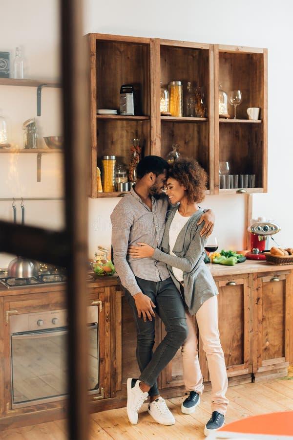Het houden van van Afrikaans-Amerikaans paar die in keuken, exemplaarruimte omhelzen stock foto