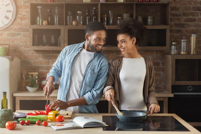 Het houden van van Afrikaans-Amerikaans paar die maaltijd in zolderkeuken voorbereiden royalty-vrije stock fotografie