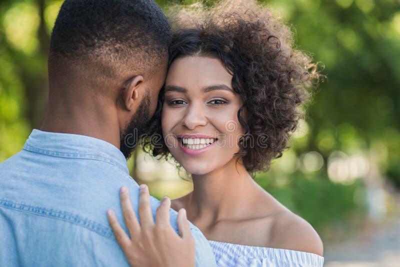 Het houden van van Afrikaans-Amerikaans paar die in het park koesteren royalty-vrije stock afbeeldingen