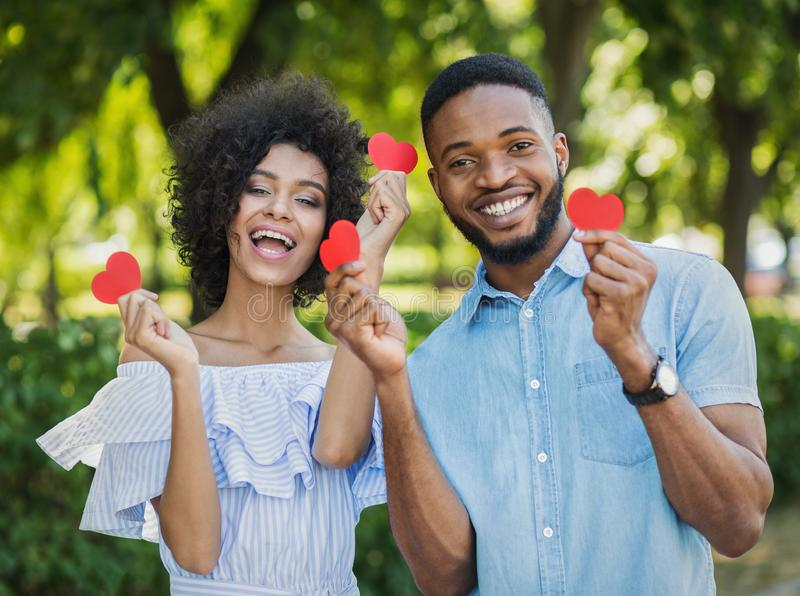 Het houden van van Afrikaans-Amerikaans paar met document harten in park royalty-vrije stock foto