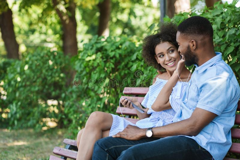 Het houden van van Afrikaans-Amerikaanse paar het luisteren muziek in park stock fotografie