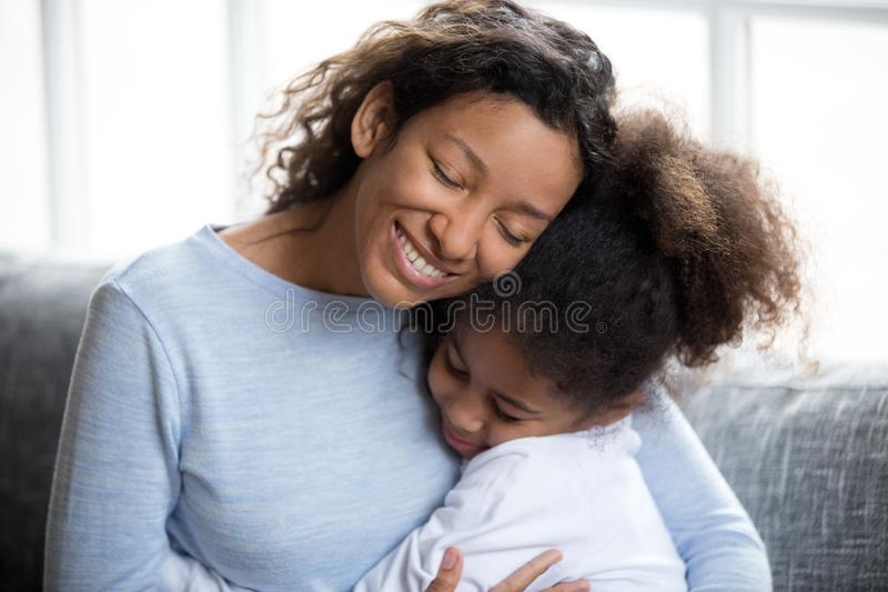 Het houden van van Afrikaanse Amerikaanse moeder die met dochter omhelzen royalty-vrije stock afbeelding