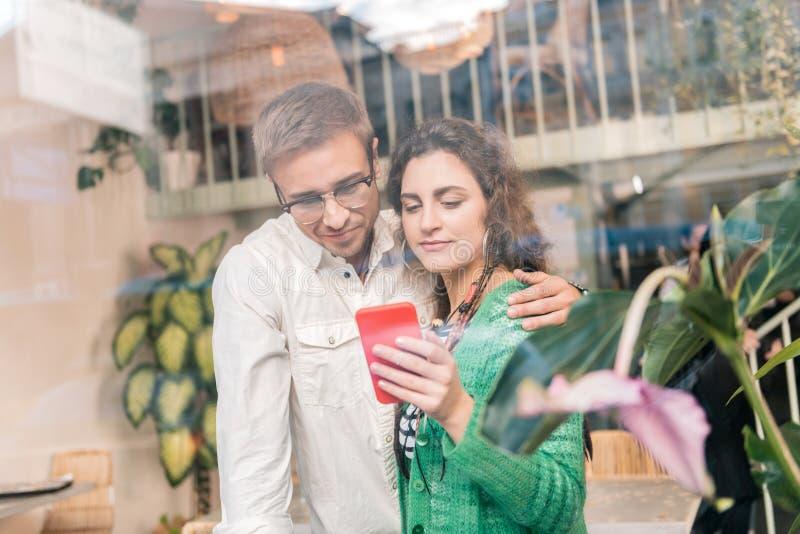 Het houden van de van gevende mens die zijn mooie vrouw koesteren die hem sommige foto's tonen royalty-vrije stock foto
