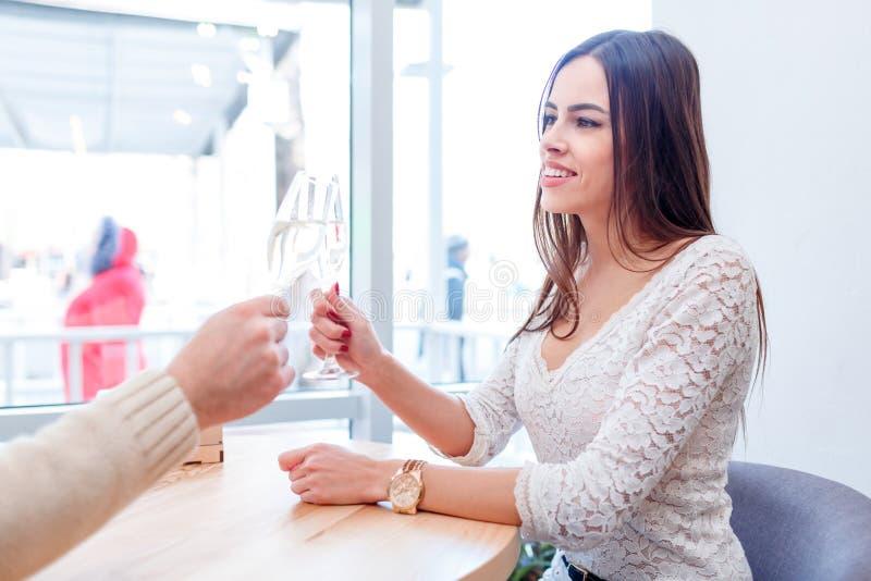 Het houden van de paarzitting in een koffie, bespreking en drinkt champagne stock fotografie