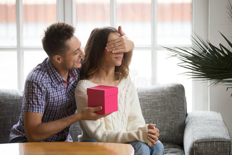 Het houden van echtgenoot van sluitende ogen van vrouw die romantische verrassing voorstellen royalty-vrije stock foto