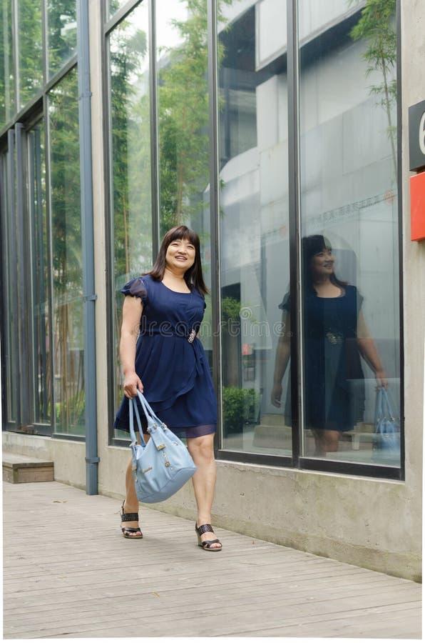 Het houden van een handtas, gelukkige vrouw die op de weg lopen stock fotografie