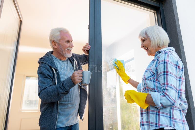 Het houden van van gebaarde blauw-eyed echtgenoot die wat thee zijn vrouwen schoonmakende deuren brengen royalty-vrije stock afbeeldingen