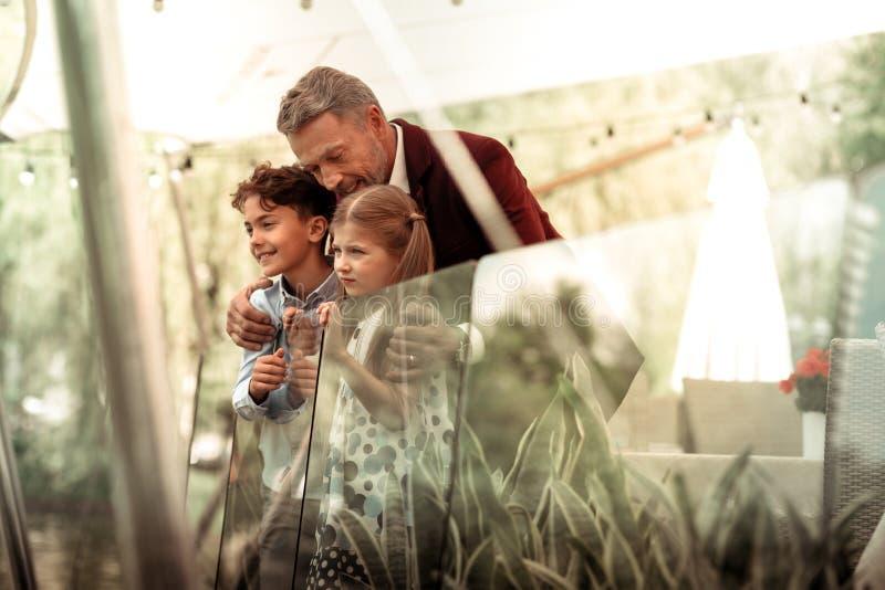 Het houden van van grijs-haired papa die zijn leuk mooi jongen en meisje koesteren royalty-vrije stock afbeelding