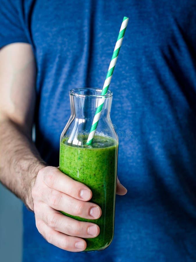 Het houden van groene smoothie Gezonde detox smoothie in handen royalty-vrije stock afbeeldingen