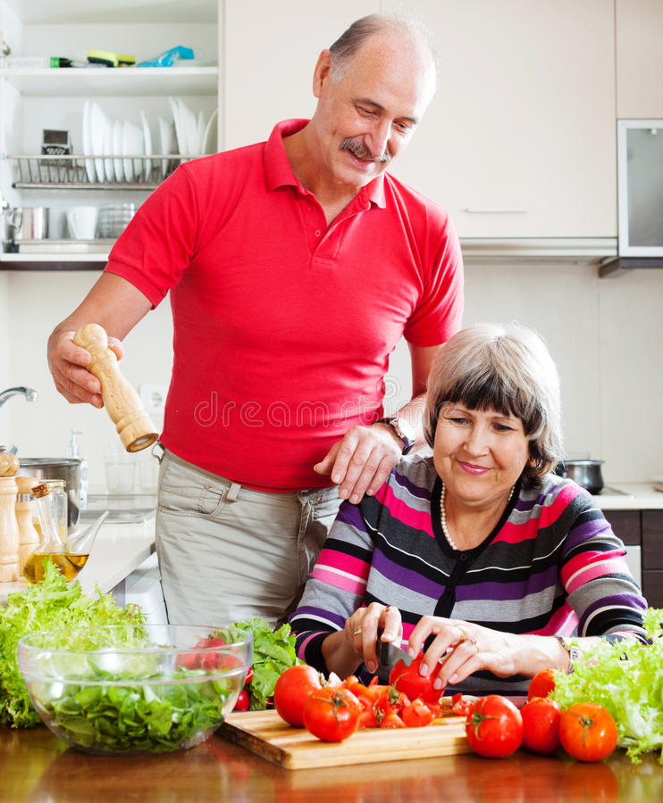 Het houden van het bejaarde paar koken met tomaten royalty-vrije stock afbeelding