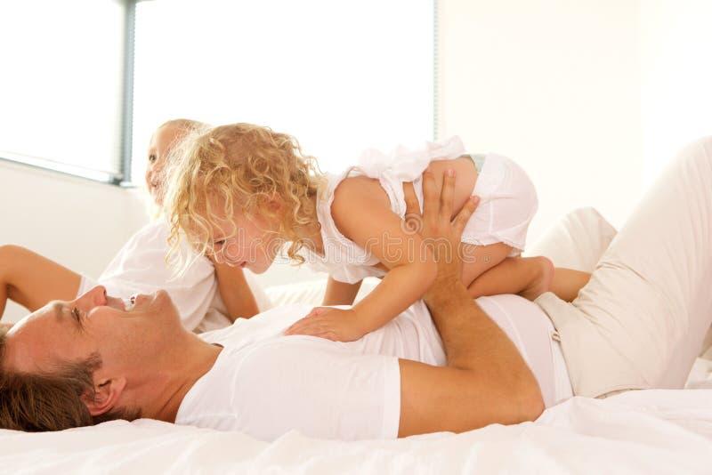 Het houden van het jonge familie spelen op bed royalty-vrije stock foto