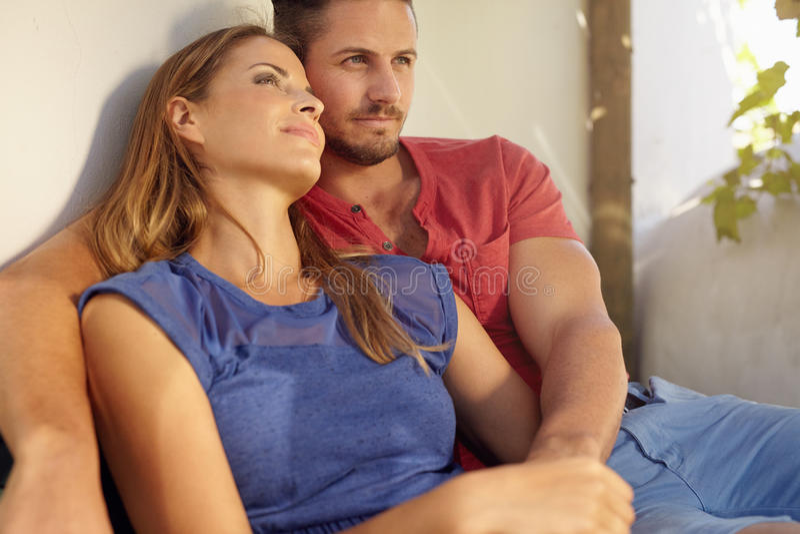 Het houden van het jonge paar ontspannen op terras stock afbeelding