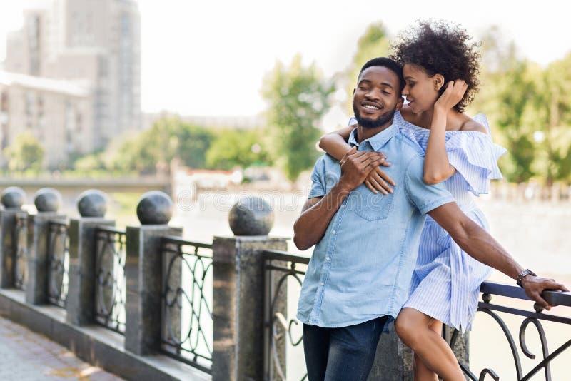 Het houden van van jong Afrikaans-Amerikaans paar die op brug omhelzen stock foto