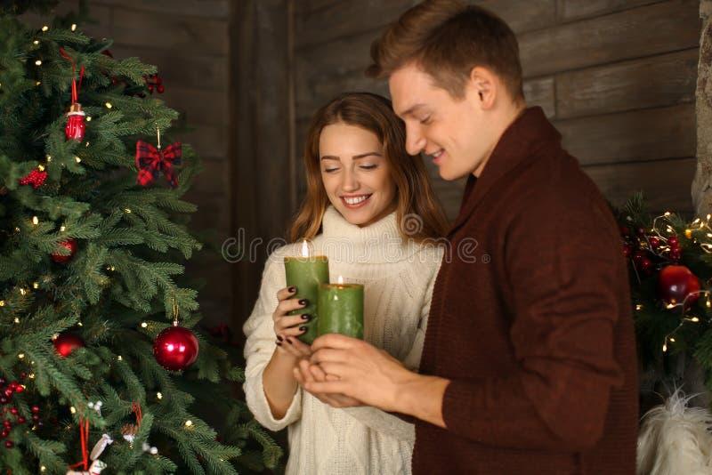 Het houden van van jong paar met het branden schouwt thuis dichtbij Kerstboom royalty-vrije stock afbeelding