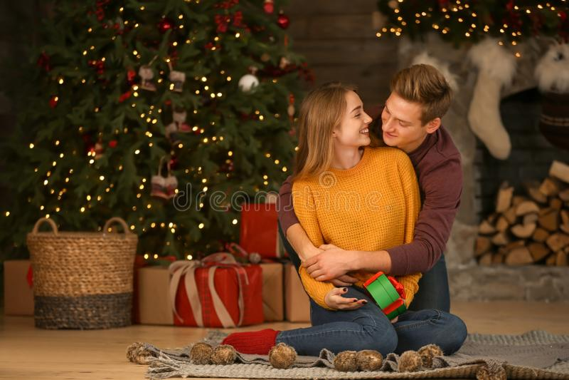 Het houden van van jong paar met gift in ruimte met Kerstmisdecor royalty-vrije stock foto's