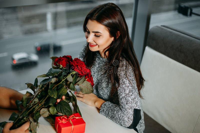 Het houden van van jong paar op datum, aantrekkelijke vrouw geworden rozen en gift royalty-vrije stock foto
