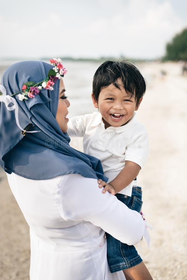 Het houden van van jonge Aziatische moeder die haar zoon houden glimlachend en lachend bij het strand royalty-vrije stock afbeelding