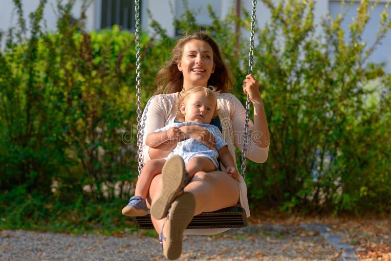 Het houden van het jonge moeder spelen met haar babyzoon stock foto