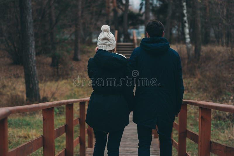 Het houden van jonge paar gelukkige samen openlucht op comfortabele gang in bos royalty-vrije stock afbeeldingen