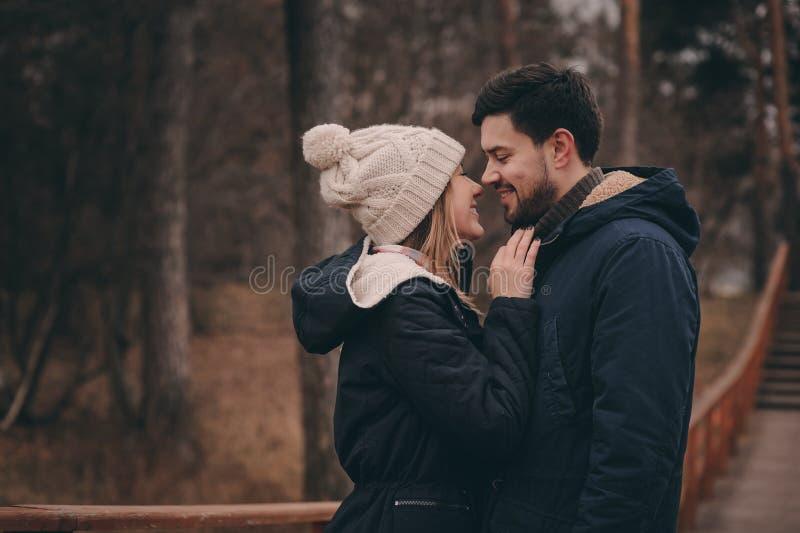 Het houden van jonge paar gelukkige samen openlucht op comfortabele warme gang in bos royalty-vrije stock foto's