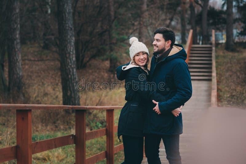 Het houden van jonge paar gelukkige samen openlucht op comfortabele warme gang in bos stock foto