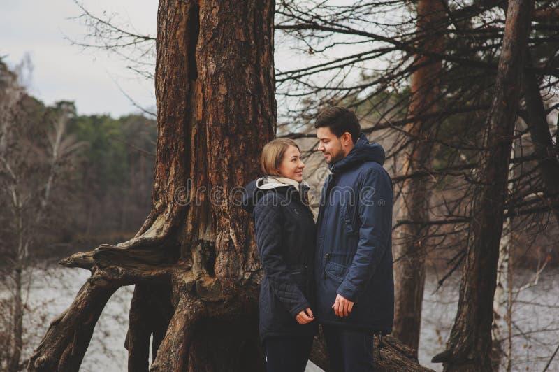 Het houden van jonge paar gelukkige samen openlucht op comfortabele warme gang in de herfstbos royalty-vrije stock foto's
