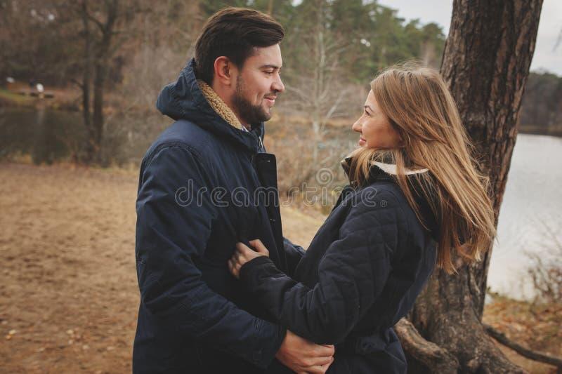 Het houden van jonge paar gelukkige samen openlucht op comfortabele warme gang in de herfstbos stock afbeeldingen
